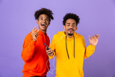 Two delighted african man friends dressed in colorful hoodies standing isolated over violet background, listening to music with earphones and mobile phone, dancing