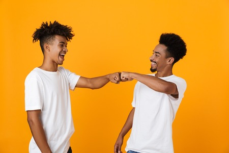 Two happy male african friends in t-shirts standing isolated over yellow background, giving fist bump