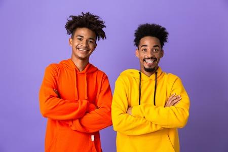 Twee gelukkige Afrikaanse mannenvrienden gekleed in kleurrijke hoodies die geïsoleerd staan over violette achtergrond, armen gevouwen