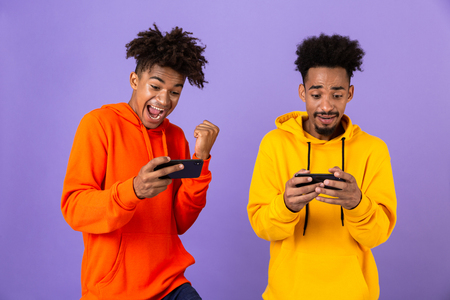 Two african man friends dressed in colorful hoodies standing isolated over violet background, playing games on mobile phones Foto de archivo