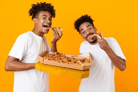 Two joyful male african friends in t-shirts standing isolated over yellow background, eating tasty pizza from a box