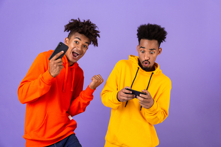 Two happy african man friends dressed in colorful hoodies standing isolated over violet background, playing games on mobile phones