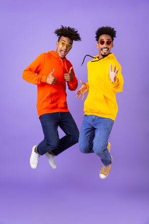 Full length of two happy male african friends in colorful hoodies jumping isolated over violet background, showing thumbs up
