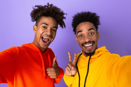 Two happy african man friends dressed in colorful hoodies standing isolated over violet background, taking a selfie