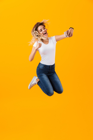 Full length image of beautiful woman jumping and taking selfie photo on mobile phone isolated over yellow background