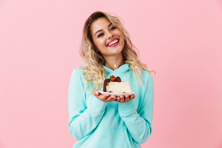Photo of happy woman in basic clothing holding piece of birthday cake with candle isolated over pink background