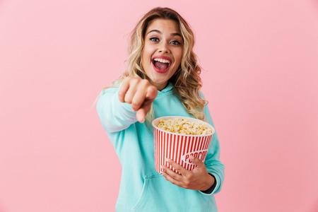 Image of cheerful european woman 20s holding bucket with popcorn and looking at camera isolated over pink background