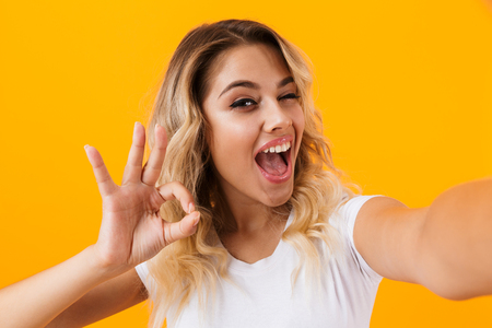 Image of young blond woman smiling and taking selfie photo isolated over yellow background Stockfoto