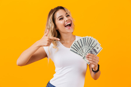 Photo of rich woman in basic clothing holding fan of dollar money isolated over yellow background Stock Photo