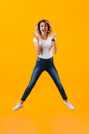 Full length photo of attractive blond woman in basic clothing jumping and laughing isolated over yellow background
