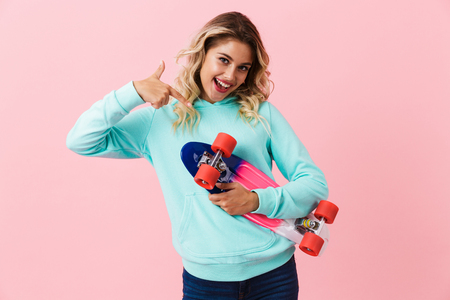 Image of skater girl 20s smiling and holding skateboard isolated over pink background