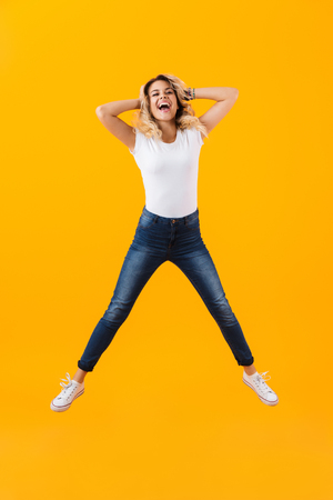 Full length photo of cheerful blond woman in basic clothing jumping and smiling isolated over yellow background