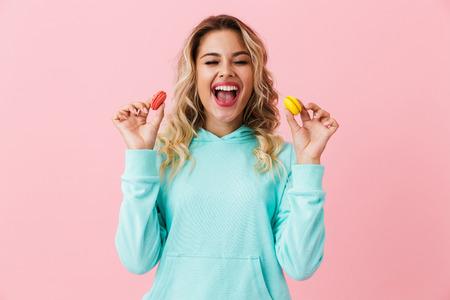 Foto der schönen Frau in der Grundkleidung, die zwei Macaron-Kekse einzeln auf rosafarbenem Hintergrund hält Standard-Bild