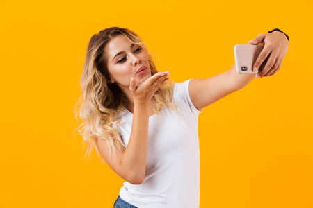 Image of caucasian young woman smiling and taking selfie photo on mobile phone isolated over yellow background Stockfoto