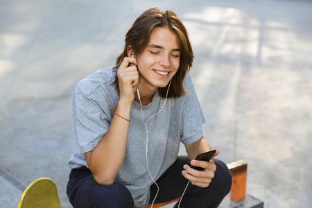 Fröhlicher junger Mann, der Zeit im Skatepark verbringt und Musik mit Kopfhörern hört
