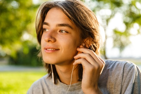 Image of cheerful young guy listening music with earphones in the park. Archivio Fotografico - 112763606