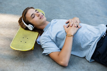 Attractive young guy spending time at the skate park, listening to music with headphones, laying on skateboard