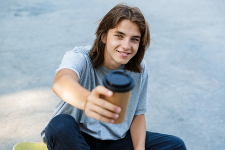 Happy young teenge boy spending time at the skate park, sitting on a skateboard, holding takeaway coffee