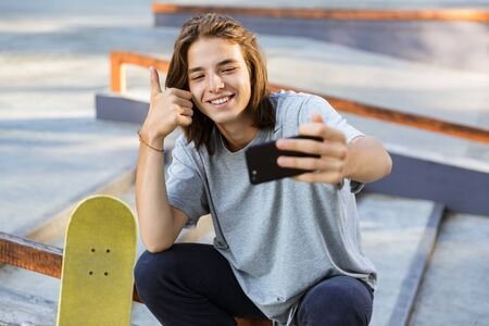 Image of cheerful young skater guy sit in the park with skateboard take selfie by mobile phone with thumbs up.