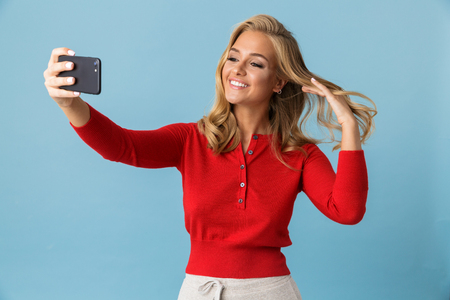 Portrait of charming blond woman 20s wearing red shirt smiling and taking selfie photo on mobile phone isolated over blue background in studio