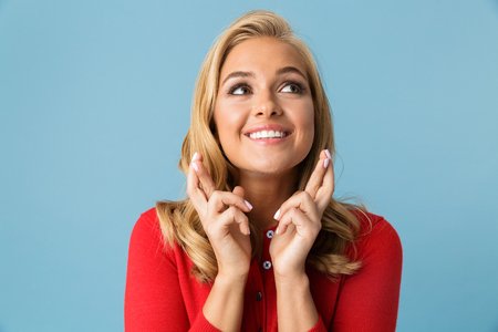 Portrait of dreaming woman 20s wearing red shirt praying with fingers crossed isolated over blue background in studio