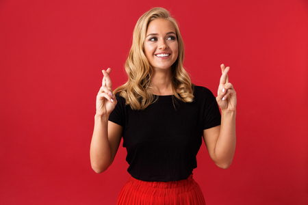 Portrait of blond woman 20s holding fingers crossed for pray or wish isolated over red background in studio