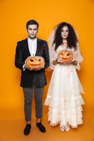 Full-length shot of young creepy halloween bride and groom in wedding costumes looking camera and holding pumpkin in web isolated over orange