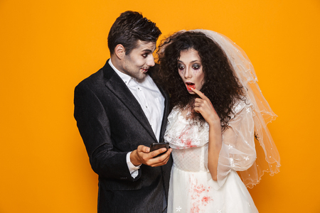 Photo of excited zombie couple bridegroom and bride wearing wedding outfit and halloween makeup using smartphone isolated over yellow background