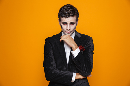Photo of scary zombie fiance on halloween wearing classical suit and creepy makeup looking at camera isolated over yellow background