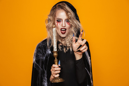 Horror wizard woman 20s wearing black costume and halloween makeup holding candle isolated over yellow background