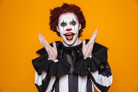 Funny man clown in costume looking camera with happiness isolated over orange