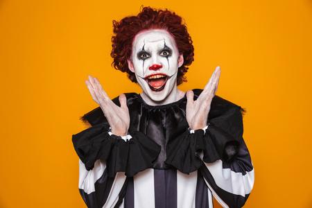 Zabawny klaun w kostiumie patrzący na kamerę ze szczęściem na białym tle nad pomarańczą