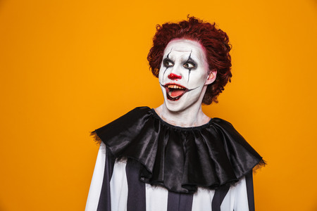 Surprised clown man 20s wearing black costume and halloween makeup looking aside isolated over yellow background