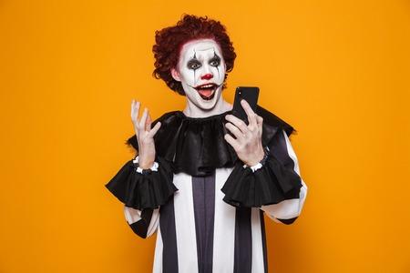 Surprised creepy man clown using smartphone isolated over orange Фото со стока
