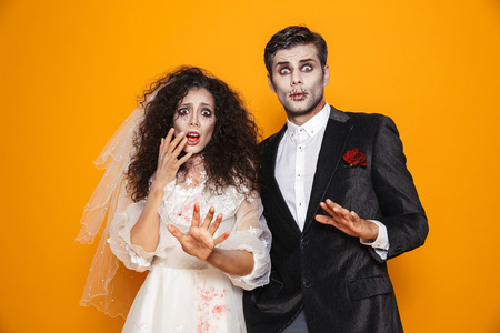 Photo of terrifying zombie couple bridegroom and bride wearing wedding outfit and halloween makeup scaring you isolated over yellow background Archivio Fotografico