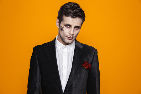 Sad brunette zombie man with halloween make-up in suit looking camera isolated over orange