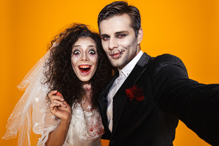 Photo of amusing zombie couple bridegroom and bride wearing wedding outfit and halloween makeup laughing while taking selfie isolated over yellow background Stockfoto