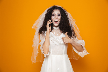 Image of dead bride zombie on halloween wearing wedding dress and scary makeup speaking on cell phone isolated over yellow background