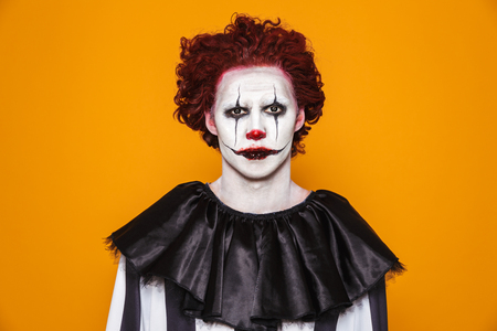 Sad clown man 20s wearing black costume and halloween makeup looking at camera isolated over yellow background Stock Photo