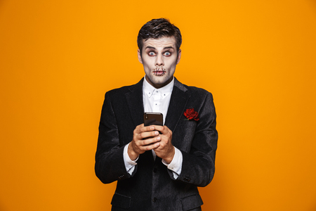 Photo of young dead gentleman on halloween wearing classical suit and creepy makeup holding mobile phone isolated over yellow background 版權商用圖片