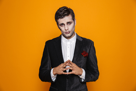 Photo of young zombie bridegroom wearing classical suit and halloween makeup looking at camera isolated over yellow background