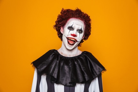 Smiling man clown with scary make up looking camera and smiling isolated oveer orange