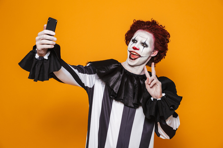 Smiling scary man clown with red hair and scary make-up making selfie on smartphone isolated over orange