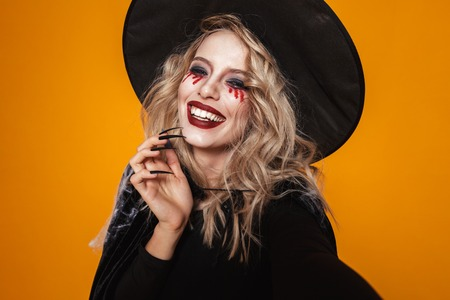 Portrait of blonde scary woman witch in black hat looking camera and smiling isolated over orange
