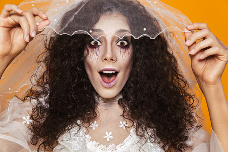 Photo of beautiful zombie woman on halloween wearing wedding dress and holiday makeup touching white veil isolated over yellow background