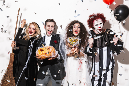 Group of cheerful friends dressed in scary costumes celebrating Halloween under confetti rain isolated over white background, holding balloons, curved pumpkin, broom