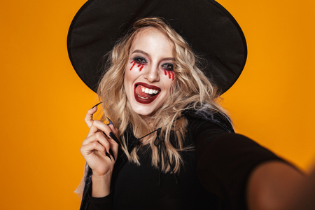 Image of glamour witch woman wearing black costume and halloween makeup smiling at camera isolated over yellow background 免版税图像 - 112484000
