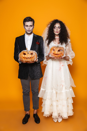 Full length photo of beautiful zombie couple bridegroom and bride wearing wedding outfit and halloween makeup holding carved pumpkin isolated over yellow background Stock Photo