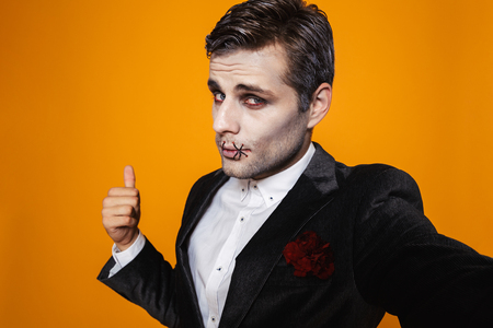 Photo of caucasian zombie man on halloween wearing classical suit and creepy makeup taking selfie isolated over yellow background