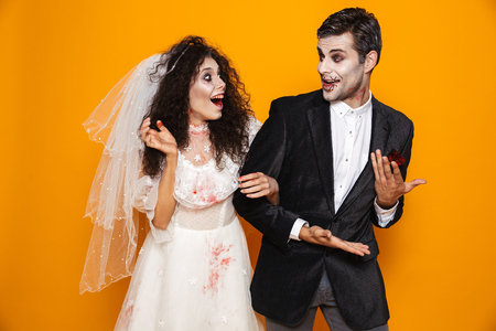 Photo of happy zombie couple bridegroom and bride wearing wedding outfit and halloween makeup laughing isolated over yellow background